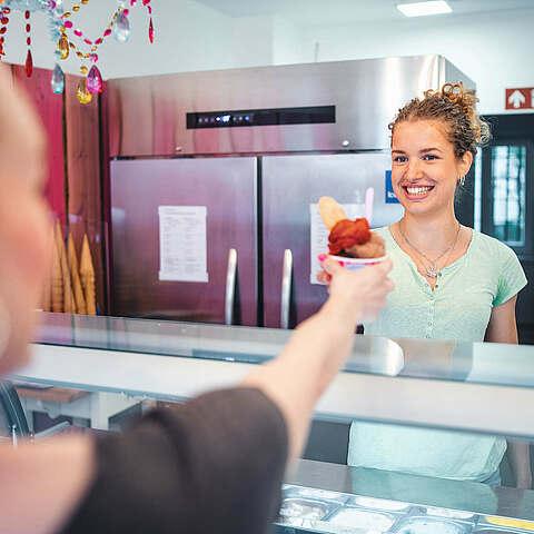 Eisverkäuferin gibt einem Gast Eis
