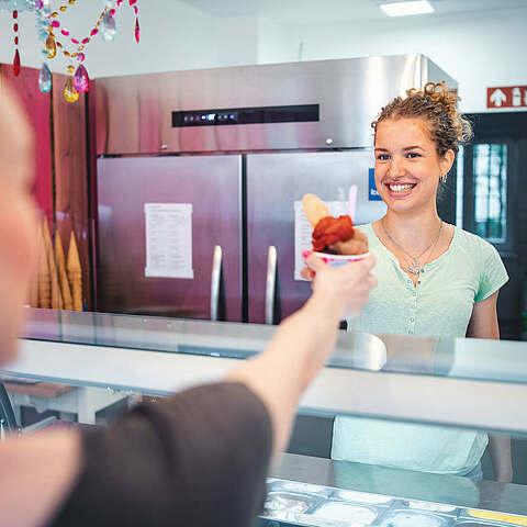 Eisverkäuferin gibt Gast ein Eis